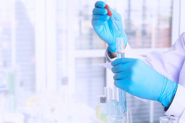 Scientist holding sampling oil or chemical liquid in flask with lab glassware in laboratory background.