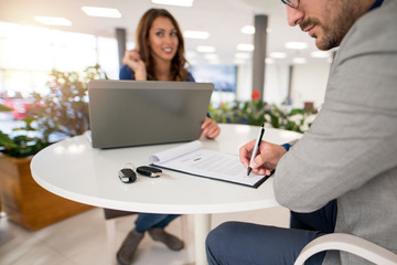 Car buyer signing a contract in vehicle dealership. Buying a new car. Car keys on the table.