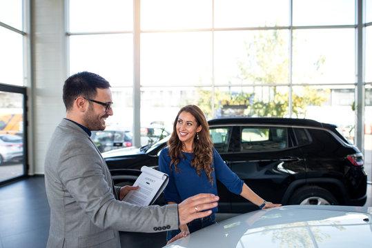 Car dealer presenting new car to the customer. Vehicle dealership.
