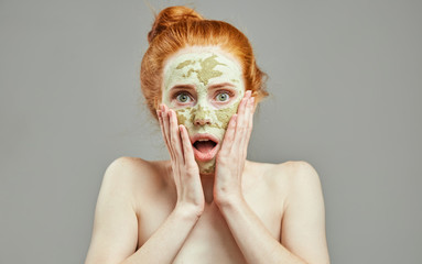 shouting girl with green mask. bad reaction on clay mask