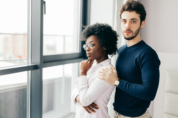 Photo of interracial couple relaxing in domestic atmosphere, have friendly talk near window in living room, dressed in casual clothes, have good relationship. Mixed race woman and man.
