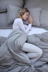Junge Frau schlafend in einem Bett