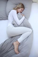 Frau im Schlafanzug liegt schlafend in ihrem Bett