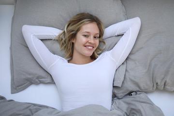 Hübsche Frau liegt lachend in ihrem Bett