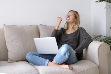 Junge Frau mit Laptop sitzt auf einem Sofa und freut sich