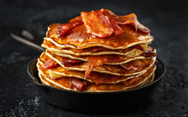 Pancakes with crispy bacon and maple syrup in cast iron skillet, frying pan. Morning Breakfast