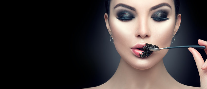 Beautiful fashion model woman eating black caviar. Beauty girl with caviar on her lips isolated on black background