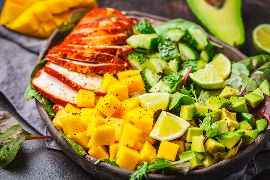 Grilled chicken, mango and avocado salad in dark dish on dark background.