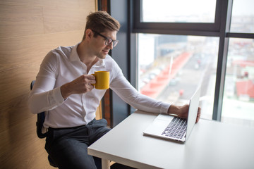 Handsome young caucasian business executive working in a bright modern office near the window, searching some information on a digital tablet and sipping coffee.