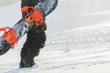 tiredness during snowboarding. tired guy is holding a snowboard and going up. side view cropped photo. copy space