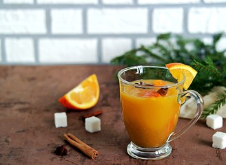 Hot sea buckthorn tea with orange and cinnamon in a glass mug on a brown background.