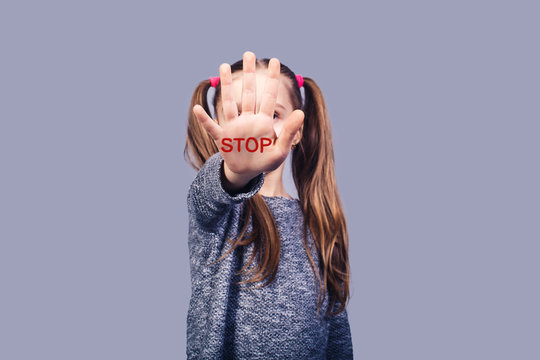 sad little girl shows hand stop sign. Concept stop child abuse.