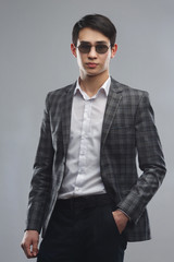 Young asian man in business suit and sunglasses isolated on gray background.