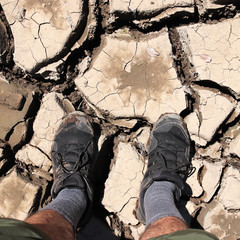 A man standing on a dry cracked river bed. Drought concept image.