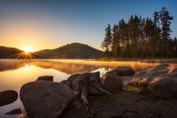 Sunrise on the lake Beautiful sunrise view with sun rays over a mountain lake surrounded by...