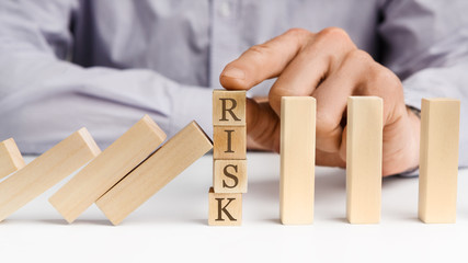 Businessman stop domino effect with word Risk
