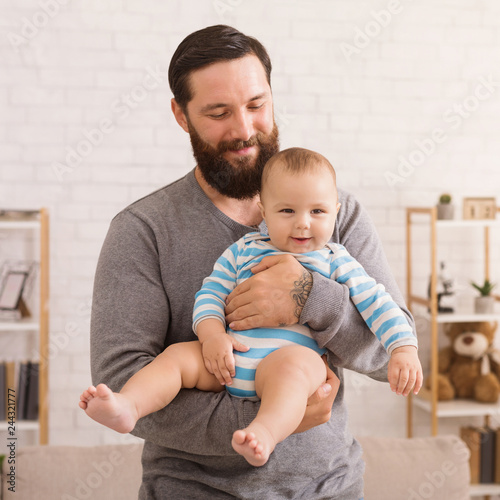 218d8373 Loving father embracing his cute baby son