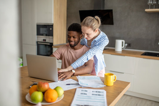 Young interracial couple using laptop together having breakfast at home, african man and european blonde woman searching for new sale offers or shopping online in the kitchen