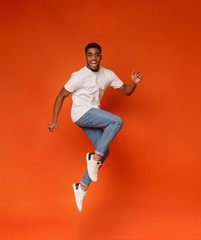 Excited african-american man jumping on orange background