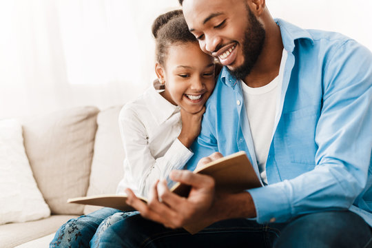 Little girl and father enjoying reading book together
