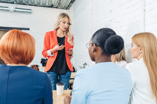 Blonde female employee make presentation for diverse employees during meeting