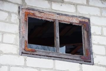 one brown window with broken glass on a gray brick wall