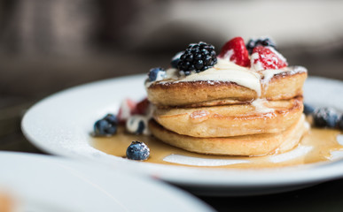 Stack of pancakes with fruit and syrup served for breakfast