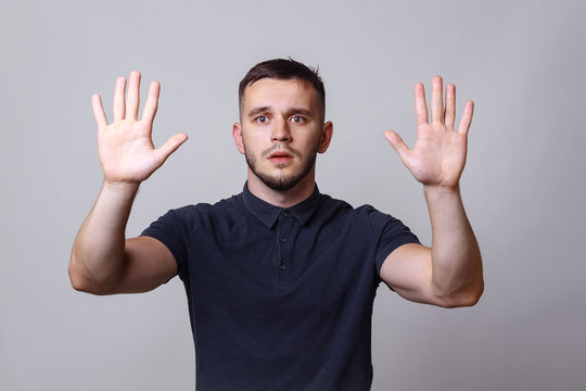 """Studio portrait of a young man keep hands up before him with the expression """"give up"""". The concept of harmony, humility, protest, humorous mood."""
