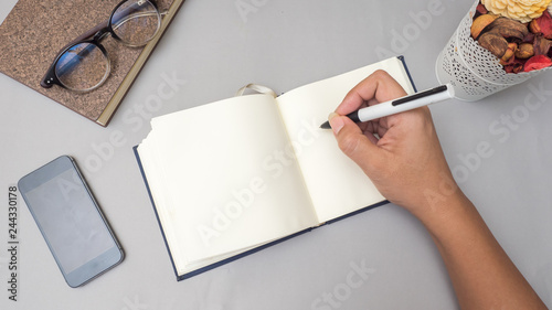 Wall mural notebook with hand on gray background business concept desk table