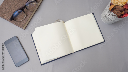 Wall mural notebook with smart phone on gray background business concept desk table