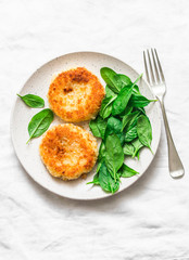 Potato bread crumbs baked cakes with spinach on a light background, top view. Delicious vegetarian lunch