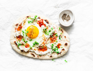 Flatbread with fried egg, yogurt, chili sauce and cheese on light background, top view