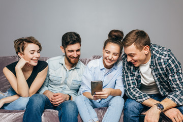 a copmany of young people are laughing at funny message. fun, happiness, joke concept