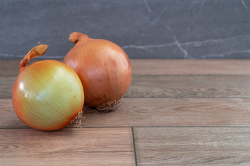 Two onions on wooden floor.