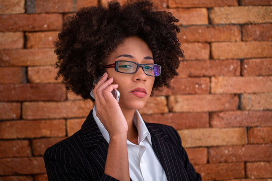 Close up portrait black business woman employee in glasses working in office talking on mobile phone