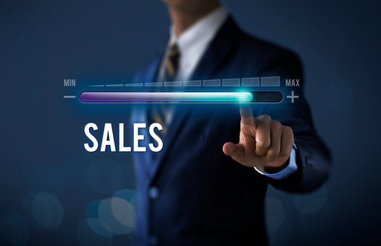 Sales growth, increase sales or business growth concept. Businessman is pulling up progress bar with the word SALES on dark tone background.