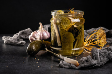 pickled cucumbers in a jar on a dark gray stone background