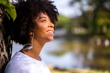 Close up portrait of an attractive african brazilian woman smiling outdoors - Imagem