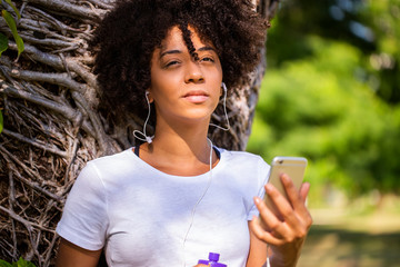 Portrait of a young african american woman listening to music on cell phone - Imagem