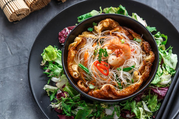 Asian salad with rice noodles with shrimps and vegetables closeup.