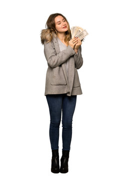 A full-length shot of a Teenager girl with coat taking a lot of money on isolated white background