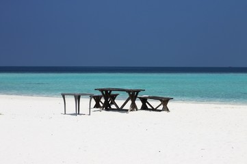 Picnic tables and bench on the shore of a desert island (Ari Atoll, maldives)