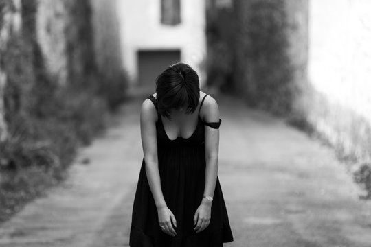 Discouraged young woman standing alone in the middle of an old street. She is dropping  her head and her arms down.