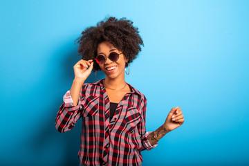 Cheerful attractive afro brazilian girl enjoying life wearing sunglasses On blue wall background - Imagem