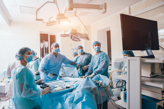 Process of gynecological surgery operation using laparoscopic equipment. Group of surgeons in operating room with surgery equipment