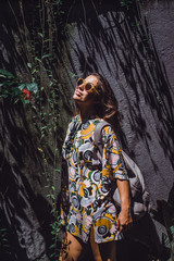 girl with a backpack, wearing sunglasses, in a tropical garden