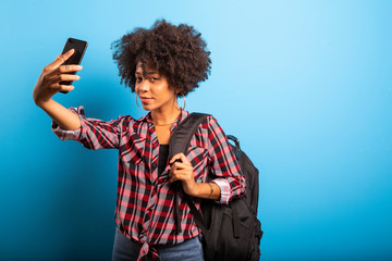 Closeup portrait of smiling young attractive African brazilian woman holding smartphone, taking selfie photo on the blue background