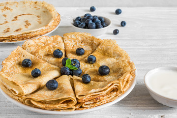 Homemade crepes or thin pancakes served with fresh blueberries, sour cream and mint