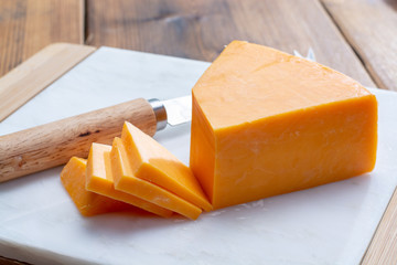 Piece of bright yellow hard cheese cheddar, originating in the English village of Cheddar in Somerset