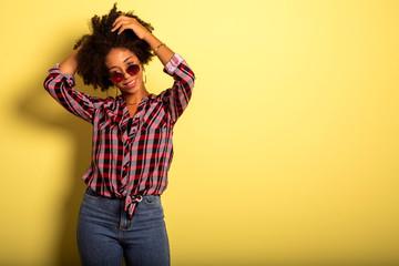 Cheerful attractive afro brazilian girl enjoying life wearing sunglasses On yellow wall background - Imagem